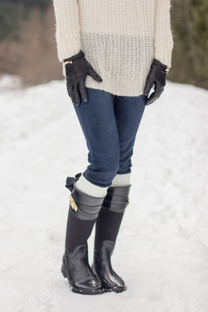 Winter sweater and rain boots in the snow